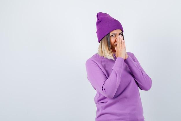 Señora bonita en suéter, gorro con las manos en gesto de oración y mirando soñadora, vista frontal.