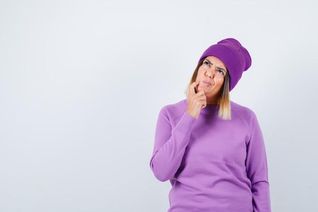 Señora bonita en suéter, gorro sosteniendo el dedo en la mejilla, mirando hacia arriba y mirando pensativo, vista frontal.