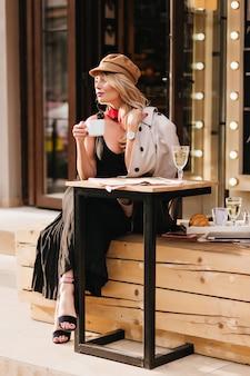 Señora bonita en vestido largo y sandalias negras disfrutando del almuerzo en la cafetería al aire libre y mirando a otro lado. fascinante chica rubia con sombrero esperando amigo para comer croissants juntos.