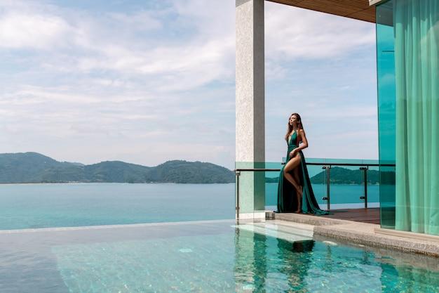 Señora bonita en un vestido de noche largo verde posando cerca de una piscina al aire libre con vistas al mar y montañas verdes