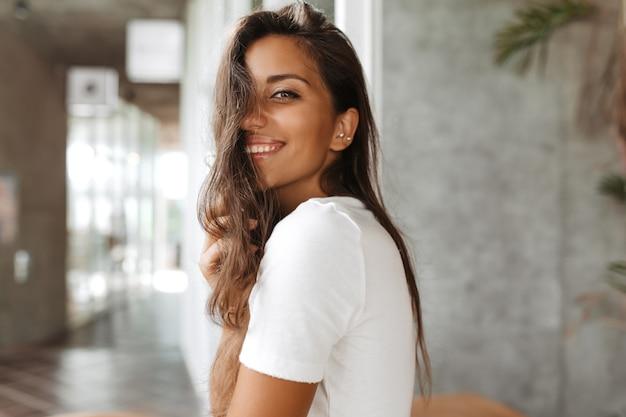 Señora bronceada con maquillaje natural está sonriendo afablemente