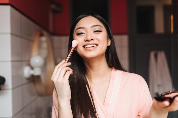 Señora de buen humor haciendo maquillaje de día