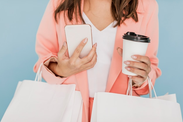 Señora con café y teléfono inteligente sobre fondo azul