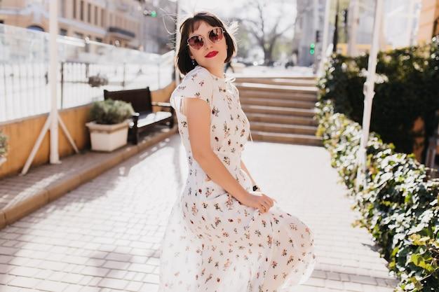 Señora caucásica alegre en gafas de sol negras caminando por la ciudad en día de verano. tiro al aire libre de chica interesada de pelo corto en vestido largo blanco escalofriante en mañana soleada de primavera.