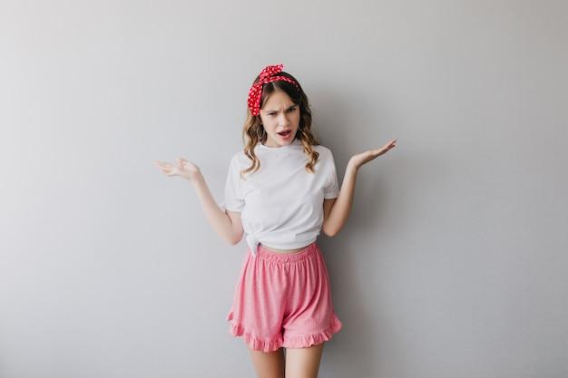 Señora caucásica emocional con cinta en el pelo agitando las manos. mujer atractiva en pantalones cortos de color rosa de pie.