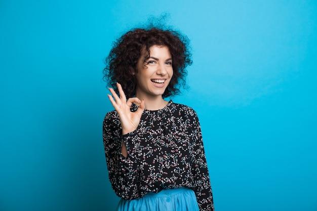 Señora caucásica de pelo rizado gesticulando bien cantar en una pared azul mientras sonríe a la cámara