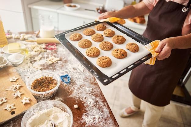 Señora cautelosa llevando una bandeja con galletas calientes a la mesa