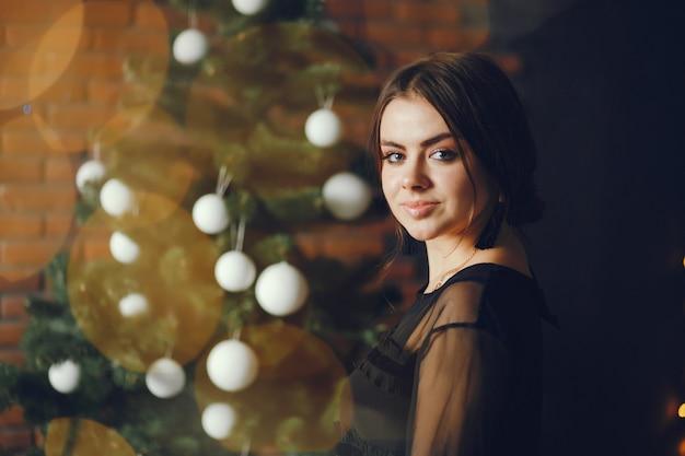 Señora cerca de un árbol de navidad.