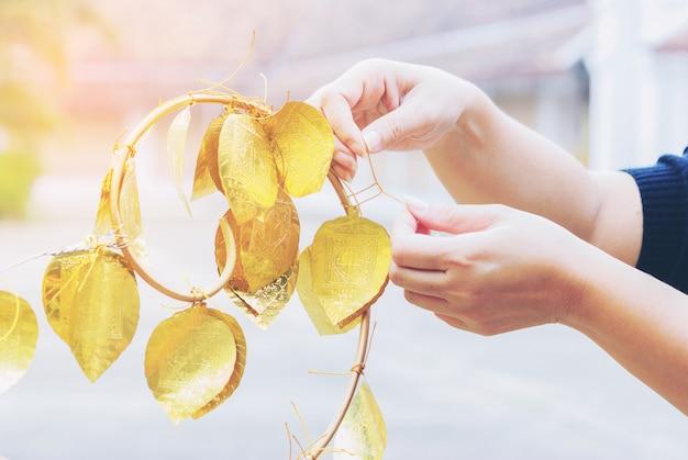 Una señora está colgando la hoja dorada de los deseos de felicidad en wat phrathat chae haeng.