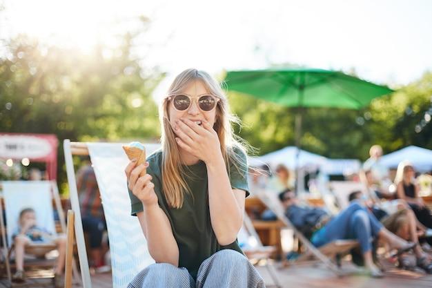 Señora comiendo helado riendo. retrato de mujer joven sentada en un parque en un día soleado comiendo helado