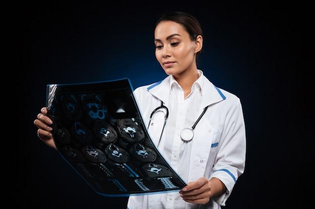 Señora concentrada joven que mira la imagen de la radiografía aislada
