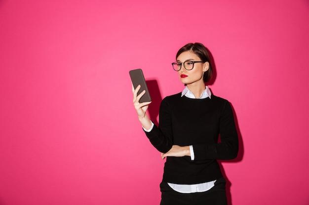 Señora confiada joven en jersey negro con smartphone aislado
