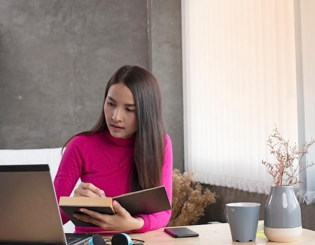 Señora control de orden de la computadora portátil y grabar en el libro