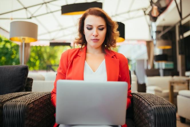 Señora de negocios exitosa mujer linda usando la computadora portátil mientras está sentado en el café salón.