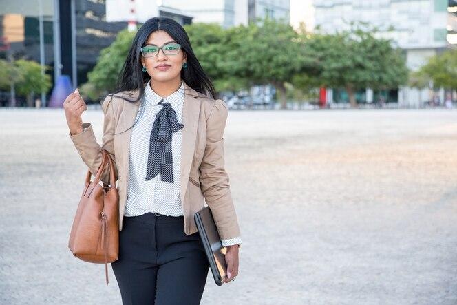 Señora de negocios serio llevando el bolso y la computadora portátil