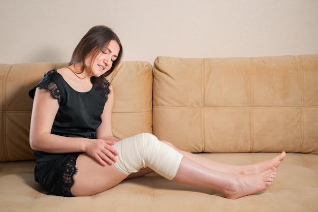 Señora descalza llorando con vendaje elástico blanco en la rodilla sentada en el sofá marrón en casa
