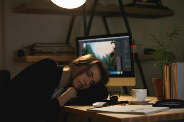 Señora diseñadora durmiendo en el espacio de trabajo