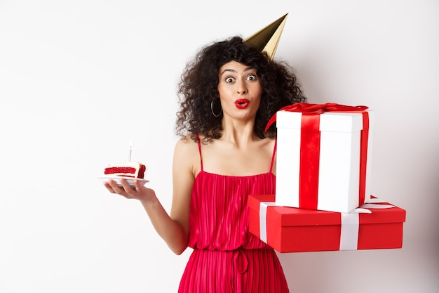 Señora divertida en vestido rojo y sombrero de fiesta, celebrando cumpleaños, sosteniendo regalos del b-day y pastel con vela, mirando divertido a la cámara, de pie sobre fondo blanco.