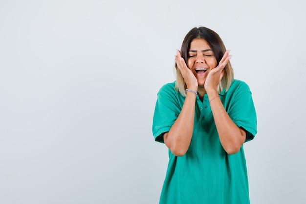 Señora elegante en camiseta de polo con las manos en las mejillas y mirando feliz, vista frontal.