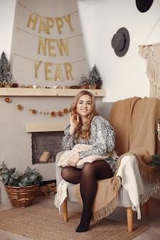 Señora elegante cerca del árbol de navidad