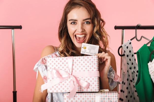 Señora elegante con compra de pie en la tienda cerca de perchero y sosteniendo una tarjeta de crédito aislada en rosa