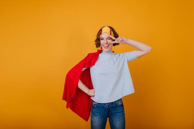 Señora elegante en corona de papel divertido posando con el signo de la paz