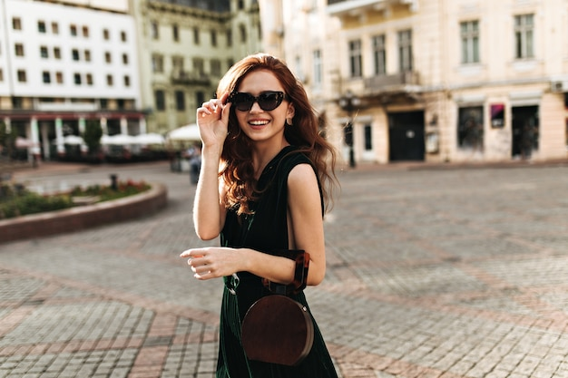 Señora elegante en gafas de sol caminando por la ciudad