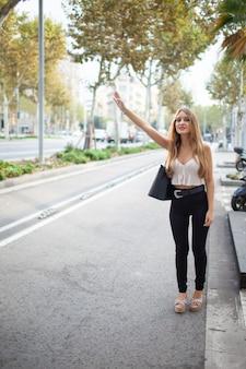 Señora elegante positiva agitando la mano mientras toma un taxi al aire libre