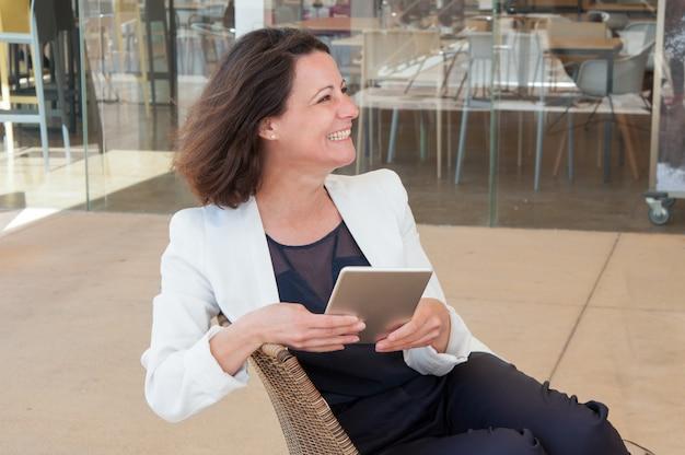 Señora elegante relajada feliz que usa la tableta