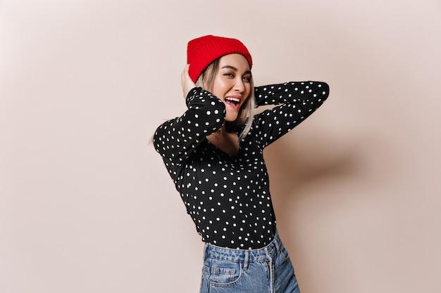Señora elegante con sombrero rojo y camisa a cuadros se divierte en la pared beige