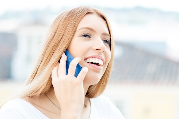 Señora emocionada que usa el teléfono móvil en viaje de negocios