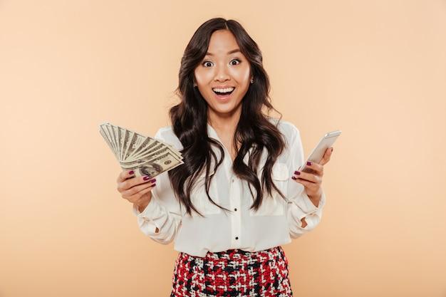 Señora emocionada con ventilador de billetes de 100 dólares en una mano y teléfono inteligente de moda en otra, sorprendida con una gran cantidad de dinero sobre fondo de durazno