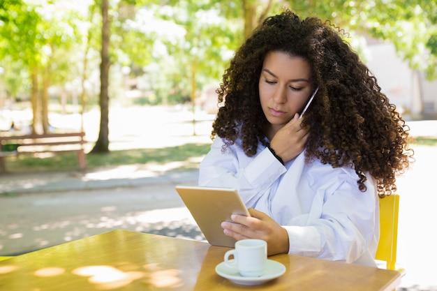 Señora enfocada llamando por teléfono y usando tableta en café al aire libre