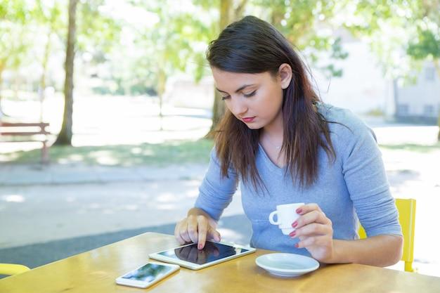 Señora enfocada tomando café y usando tableta en café al aire libre