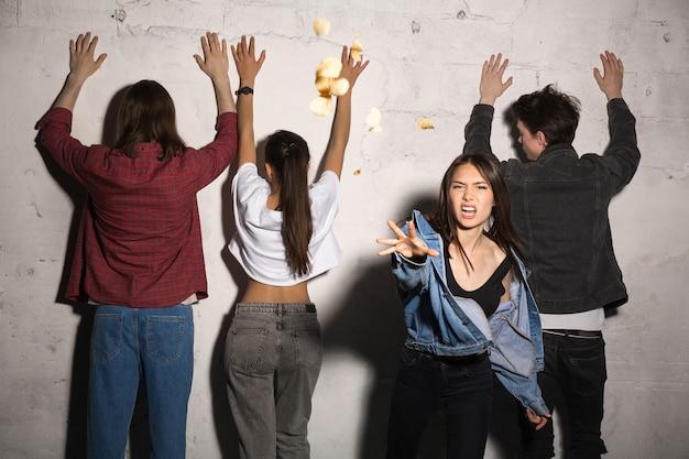 Señora enojada de pie y arrojando pan con amigos