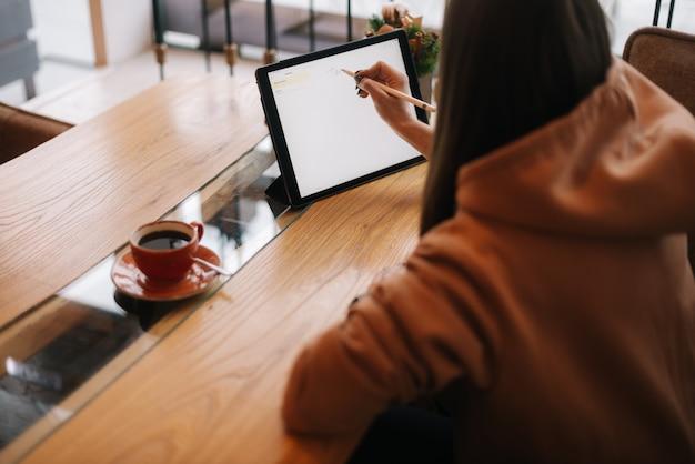 Señora escribiendo con un lápiz en una tableta digital en la mesa en un acogedor café en el fondo de la ventana
