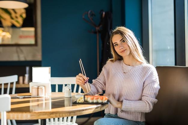 Señora estudiante en suéter blanco comiendo sushi para el almuerzo en una pequeña cafetería