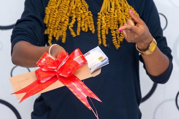 La señora extiende un sobre envuelto con una cinta roja que contiene algo de dinero en efectivo.