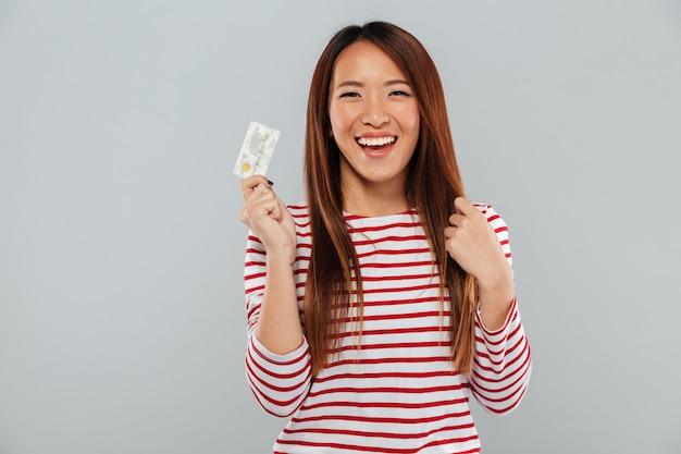 Señora feliz asiática que se coloca aislada sobre la pared gris