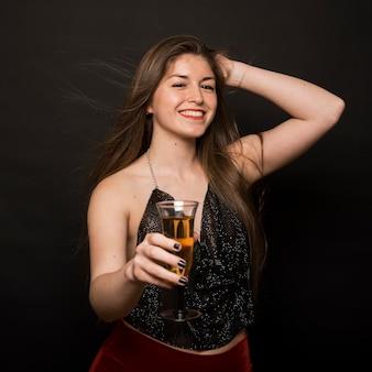 Señora feliz atractiva en paño de la tarde con el vidrio de la bebida y la mano en la cabeza