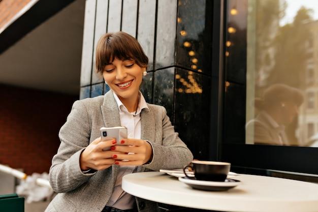 Señora feliz atractiva en traje elegante con smartphone. mujer morena bronceada en chaqueta gris se sienta afuera con teléfono, vaso de café y computadora portátil.