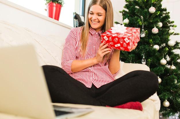 Señora feliz con caja de regalo cerca de portátil y árbol de navidad