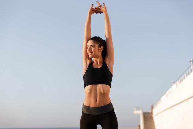 Señora feliz fitness estirando las manos mientras entrena cerca del mar