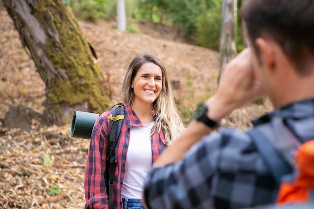 Señora feliz posando y sonriendo en el camino en el bosque. hombre irreconocible tomando la foto de su novia. turistas caminando juntos en el bosque y divirtiéndose. concepto de turismo, aventura y vacaciones de verano.