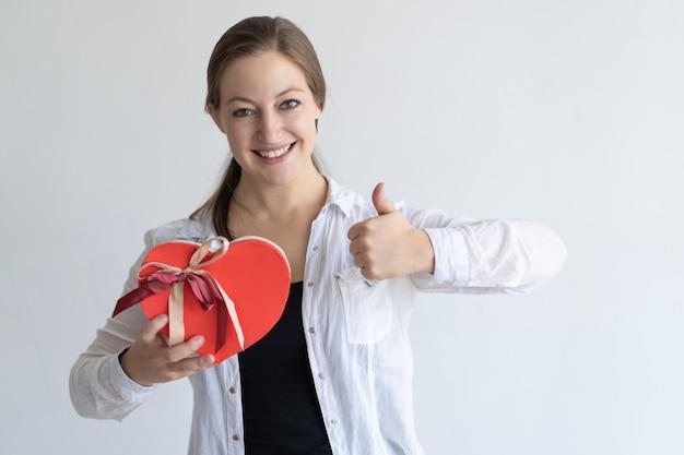 Señora feliz que muestra la caja y el pulgar en forma de corazón de regalo para arriba