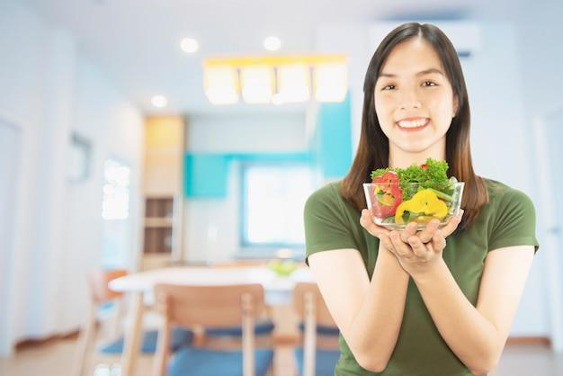 Señora feliz que sostiene cosas de la cocina sobre fondo del espacio de la copia