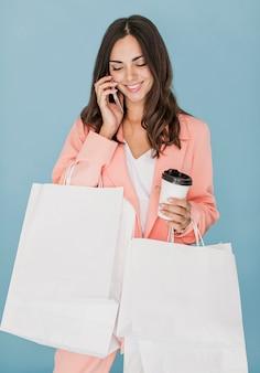 Señora feliz con redes de compras hablando en el teléfono inteligente