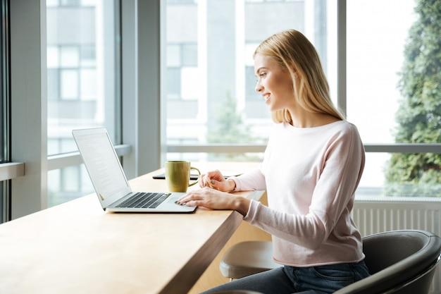 Señora feliz sentada en la oficina de coworking mientras usa la computadora portátil