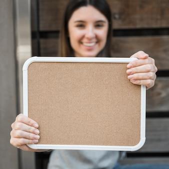 Señora feliz con tableta de madera