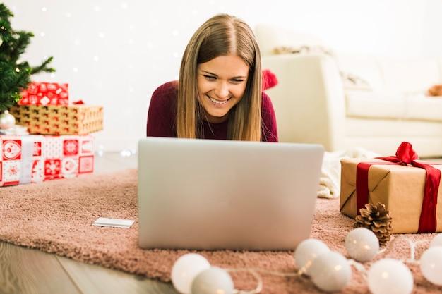 Señora feliz usando una laptop cerca de cajas de regalo y luces de colores